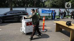 Petugas membawa peralatan medis saat hari pertama pengoperasian Rs Darurat Covid Asrama Haji Pondok Gede, Jakarta, Sabtu (10/7/2021). Presiden Joko Widodo secara resmi mengumkan asara haji pondok gede difungsikan sebagai rumah sakit darurat Covid-19 pada Jumat (9/7). (Liputan6.com/Faizal Fanani)