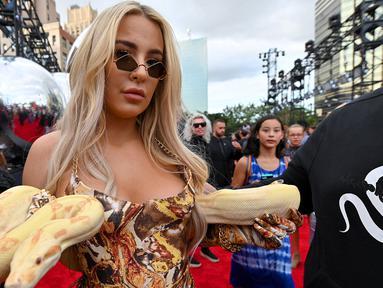 Tana Mongeau berpose saat menghadiri MTV VMA's 2019 di New Jersey, AS (26/8/2019). Bintang YouTuber Tana Mongeau menjadi pusat perhatian karena sensasinya membawa seekor ular di acara tersebut. (Dia Dipasupil/Getty Images for MTV/AFP)