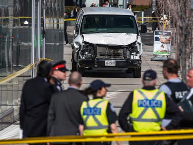 Aparat polisi berdiri dekat sebuah van yang menabrak para pejalan kaki di persimpangan utama di pinggiran utara Toronto, Kanada, Senin (23/4). Sembilan orang tewas dan 16 lainnya terluka dalam insiden itu. (Aaron Vincent Elkaim/The Canadian Press via AP)