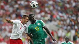 Bek Polandia, Thiago Cionek, duel udara dengan gelandang Senegal, Alfred Ndiaye, pada laga Piala Dunia di Stadion Spartak, Selasa (19/6/2018). Senegal menang 2-1 atas Polandia. (AP/Darko Vojinovic)