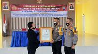 Direktur Lemkapi Dr Edi Hasibuan menyerahkan penghargaan kepada Polres Kampar karena terobosan pelayanan saat pandemi Covid-19 di Riau. (Liputan6.com/M Syukur)