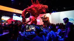 "Di bawah patung raksasa Goliath, para pengunjung memainkan video game baru ""Evolve"" yang ikut dipamerkan dalam Electronic Entertainment Expo (E3), di Los Angeles, Amerika Serikat, (10/6/2014). (REUTERS/Kevork Djansezian)"