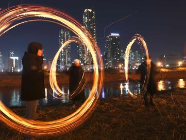 "Peserta memutar kaleng arang yang terbakar menjelang perayaan ""Jeongwol Daeboreum"" (Bulan Purnama) di sebuah taman di Seoul, Korea Selatan (1/3). Permainan ini dipercaya dapat menyuburkan tanah dan menyingkirkannya hama. (AFP Photo/Jung Yeon-je)"