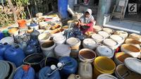 Seorang ibu mengisi air pada antrean jeriken di sumur Masjid di Kampung Citapen, Desa Weninggalih, Bogor, Rabu (24/07/2019). Sekitar 4000 jiwa warga Desa Weninggalih mengalami kesulitan mendapatkan air bersih akibat musim kemarau sejak tiga bulan terakhir. (merdeka.com/Arie Basuki)