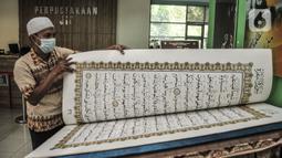 Petugas membaca sepenggal ayat dari Alquran raksasa koleksi Perpustakaan Jakarta Islamic Center (JIC), Jakarta Utara, Kamis (22/4/2021). Alquran tersebut berukuran 142 cm x 95 cm dan terdiri dari 604 halaman. (merdeka.com/Iqbal S Nugroho)