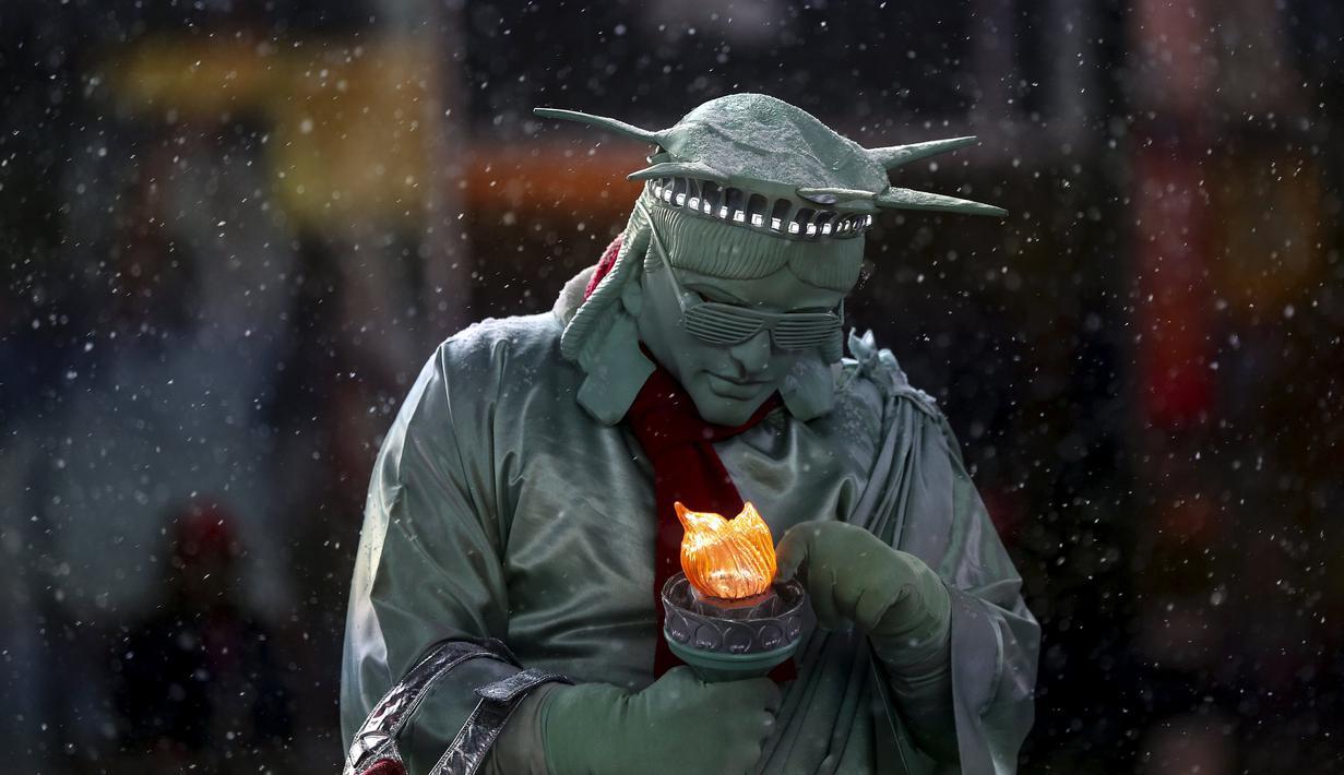 """Seorang pria berpakaian seperti """"Patung Liberty"""" memperbaiki lampu yang dipegangnya saat salju turun di Times Square di Manhattan borough New York, (22/1/2016). (REUTERS/Carlo Allegri)"""