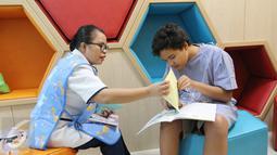 Perawat sedang membantu pasien anak membuat prakarya dalam rangka merayakan Paskah di Rumah Sakit Siloam Semanggi, Jakarta, Minggu (16/04).(Liputan6.com/Fery Pradolo)