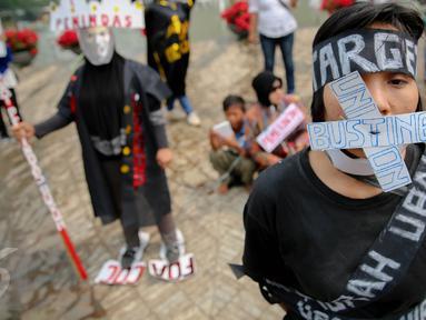 Seorang buruh melakukan aksi teatrikal di Bundaran HI, Jakarta, Kamis (20/8/2015). Dalam aksinya mereka menuntut Panarub Dwikarya, buyer Adidas dan Mizuno menyelesaikan kasus PHK massal  terhadap 1.300 pekerja. (Liputan6.com/Faizal Fanani)