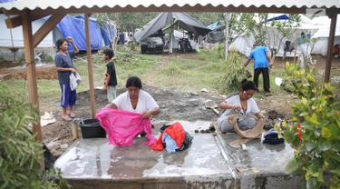 Warga pengungsi Gunung Agung mencuci pakaian di MCK sementara di Posko Pengungsi Rendang, Bali, Sabtu (2/12). Warga terpaksa memanfaatkan MCK seadanya yang berada di sekitar pengungsian. (Liputan6.com/Immanuel Antonius)