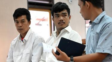 Warga negara Thailand, Prakob Seetasang (kiri) dan Adison Phonlamat (tengah) saat menjalani persidangan kasus penyelundupan narkoba di pengadilan Denpasar, Bali (23/9/2019). Jaksa menuntut 2 pria Thailand tersebut dengan hukuman penjara 18 tahun. (AFP Photo/Sonny Tumbelaka)