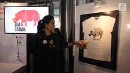 Artis Marcella Zalianty menunjuk karya dalam pameran seni badak Sumatera di Perpustakaan Nasional Indonesia, Jakarta Pusat, Jumat (19/1). Sebanyak 10 seniman muda Indonesia dan Internasional berpartisipasi dalam pameran ini. (Liputan6.com/Arya Manggala)