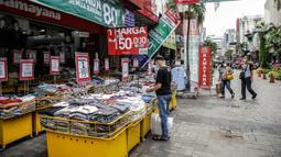 Pengunjung melihat pakaian yang dijajakan di salah satu tenant di Pasar Baru, Jakarta, Rabu (5/4/2021). Selama pandemi COVID-19, tak banyak orang yang mau berbelanja di luar rumah. (Liputan6.com/Faizal Fanani)