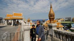 Pengunjung memasuki kawasan kuil Golden Budha di kota Bangkok, Thailand, Sabtu (17/12). Salah satu biksu yang ada di kuil tersebut memprediksi hasil laga final kedua Piala AFF 2016 antara Thailand melawan Indonesia. (Liputan6.com/Helmi Fithriansyah)