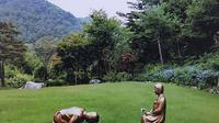 Patung seorang pria bersujud ke wanita penghibur Korea di The Korea Botanical Garden. Dok: AP Photo