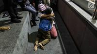 Terpidana kasus dugaan pelanggaran UU ITE sekaligus korban pelecehan seksual Baiq Nuril sujud syukur bersama putranya setelah DPR menyetujui amnesti untuk dirinya dalam rapat paripurna di Kompleks Parlemen Senayan, Jakarta, Kamis (25/7/2019). (Liputan6.com/JohanTallo)