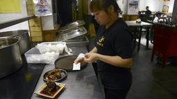 Seorang pelayan menyiapkan menu kepala kelinci di sebuah restoran di Chengdu, ibu kota Provinsi Sichuan di barat daya China, 8 September 2016. Otak kelinci di negeri tirai bambu ini menjadi salah satu menu favorit warga lokal maupun asing. (WANG ZHAO/AFP)