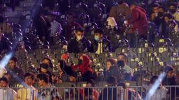 Penggemar gulat mengenakan masker ketika mereka menonton pertandingan gulat WWE Super ShowDown di Riyadh, Arab Saudi, Kamis (27/2/2020). Pertandingan gulat ini diadakan di tengah epidemi virus corona COVID-19  yang telah menyebar hampir ke seluruh penjuru dunia. (AP Photo/Amr Nabil)