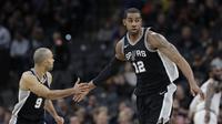 Pemain San Antonio Spurs, LaMarcus Aldridge (12) dan rekannya Tony parker (9) merayakan keberhasilan mencetak poin  pada lanjutan NBA di basketball game di AT&T Center, San Antonio, (23/1/2018). Spurs menang atas Cleveland 114—102. (AP/Eric Gay)