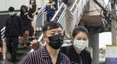 Pekerja mengenakan masker usai menaiki komuter selama kabut asap menyelimuti Bangkok (16/1). Thailand telah berupaya untuk mengatasi polusi yang telah menyelimuti ibukota dalam beberapa pekan terakhir. (AFP Photo/Romeo Gacad)