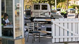 Penyidik kepolisian mewawancarai saksi mata setelah mobil van yang menabrak kerumunan orang di depan sebuah restoran di Los Angeles, Minggu (30/7). Sopir kendaraan itu telah ditangkap dan dibawa ke rumah sakit untuk diperiksa (AP Photo/Damian Dovarganes)