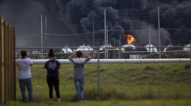Warga mengamati kebakaran pabrik TPC Group yang meledak di Port Neches, Texas (27/11/2019). Dua ledakan besar 13 jam terpisah membakar pabrik kimia dan menyebabkan tiga pekerja terluka. (Marie D. De Jesús/Houston Chronicle via AP)