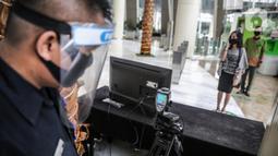 Petugas melihat alat pendeteksi suhu tubuh di Mal Central Park, Jakarta, Rabu (3/6/2020). Selain menerapkan protokol kesehatan ketat, pusat perbelanjaan juga menyediakan fasilitas pendukung 'physical distancing' sebagai persiapan operasional di era normal baru. (Liputan6.com/Faizal Fanani)
