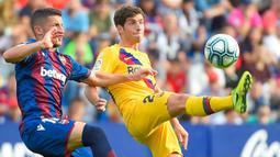 Gelandang Levante, Enis Bardhi, berusaha merebut bola dari bek Barcelona, Sergi Roberto, pada laga La Liga Spanyol di Stadion Ciutat de Valencia, Valencia, Sabtu (2/11). Levante menang 3-1 atas Barcelona. (AFP/Jose Jordan)