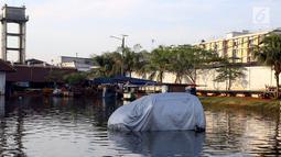 Sebuah mobil terparkir di jalanan yang terendam banjir rob di kawasan Muara Baru, Penjaringan, Jakarta Utara, Kamis (7/12). Rob tinggi membuat tanggul tidak mampu menahan air laut sehingga membanjiri jalanan. (Liputan6.com/Johan Tallo)