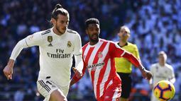 Gelandang Real Madrid, Gareth Bale, berebut bola dengan bek Girona, Jonas Ramalho, pada laga La Liga di Stadion Santiago Bernabeu, Madrid, Minggu (17/2). Madrid kalah 1-2 dari Girona. (AFP/Gabriel Bouys)