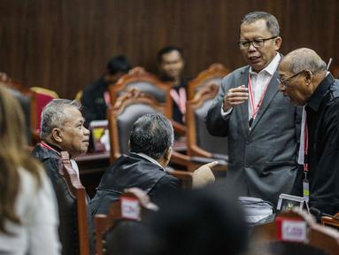 Anggota tim hukum Joko Widodo-Ma'ruf Amin, Luhut Pangaribuan (kiri) berbincang jelang sidang lanjutan sengketa Pilpres 2019 di Gedung MK, Jakarta, Kamis (20/6/2019). Sidang beragenda mendengarkan keterangan saksi dan ahli dari pihak termohon Komisi Pemilihan Umum (KPU). (Liputan6.com/Faizal Fanani)