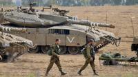 Tentara Israel berjalan melewati tank di dekat perbatasan Gaza-Israel, Jumat (19/10). PM Benjamin Netanyahu berjanji bakal mengambil tindakan tegas apabila warga Palestina masih terus melancarkan serangan ke wilayah Israel. (AP Photo/Ariel Schalit)