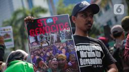 Massa membawa poster bertuliskan 'Stop Genocide' saat menggelar aksi Solidaritas untuk Muslim Uighur di depan Kedutaan Besar China di Jakarta, Jumat (20/12/2019). Mereka mengecam dan mengutuk keras penindasan terhadap muslim Uighur di China. (Liputan6.com/Faizal Fanani)