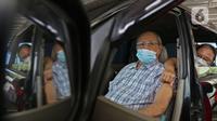 Warga lanjut usia (lansia) menunggu untuk menerima vaksinasi Covid-19 secara drive-thru di area parkir Hall C JIExpo Kemayoran, Jakarta, Rabu (3/3/2021). Layanan vaksinasi drive thru ini hanya untuk lansia atau warga DKI Jakarta yang berusia 60 tahun ke atas. (Liputan6.com/Herman Zakharia)