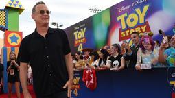 """Tom Hanks berpose saat tiba menghadiri pemutaran perdana film """"Toy Story 4"""" di El Capitan di Los Angeles (11/6/2019). Tom Hanks mengisi suara sebagai Woody di film tersebut. (AP Photo/Chris Pizzello)"""