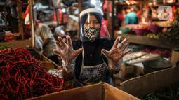 Salah satu pedagang menggunakan face shield dan sarung tangan saat melayani pembeli di Pasar Senen, Jakarta, Senin (1/6/2020). Saat era new normal, para pedagang di pasar rakyat diwajibkan menggunakan masker, face shield, dan sarung tangan selama beraktivitas. (Liputan6.com/Faizal Fanani)