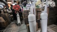 Pedagang membawa tabung oksigen ukuran 1 kubik yang sudah dipesan pembeli di Pasar Pramuka, Jakarta, Kamis (24/6/2021). Kelangkaan tabung oksigen  akibat meningkatnya permintaan seiring lonjakan kasus Covid-19 di Ibu Kota. (merdeka.com/Iqbal S. Nugroho)