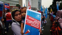 Seorang buruh membawa anak saat melakukan aksi di depan Kedutaan besar Jerman di Jakarta, Selasa (18/7). Mereka menuntut PT Panarub Dwikarya karena dinilai telah berlaku tidak adil pada buruh yang bekerja di perusahan tersebut. (Liputan6.com/Angga Yuniar)