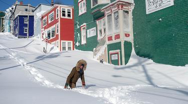Warga berjalan melewati salju di Kota St John's, Newfoundland, Kanada, Sabtu (18/1/2020). St John's menghadapi keadaan darurat ketika salju tebal memaksa pusat-pusat bisnis tutup dan kendaraan dilarang melintas di jalan raya. (Andrew Vaughan/The Canadian Press via AP)