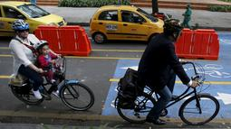 "Dua orang pengguna sepeda melintas di persimpangan lampu merah selama ""No Car Day"" di Bogota, Kolombia (4/2/2016). Selama "" No Car Day"" Jalur ini juga dapat dilalui para pengguna sepatu roda dan skateboard. (REUTERS/John Vizcaino)"