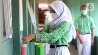 Murid mencuci tangan saat belajar tatap muka dengan penerapan protokol kesehatan COVID-19 di SMAN 2 Cibinong, Kabupaten Bogor, Jawa Barat, Rabu (17/3/2021). Sebanyak 170 sekolah di Kabupaten Bogor mulai menggelar uji coba pembelajaran secara tatap muka hingga 10 April 2021. (merdeka.com/Arie Basuki)