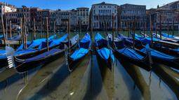 Perairan yang lebih jernih terlihat saat sejumlah gondola terparkir di Grand Canal Venesia pada 18 Maret 2020. Sejak Italia memberlakukan lockdown akibat pandemi virus corona, air di Kanal Venesia yang biasanya keruh dan gelap berubah menjadi jernih. (ANDREA PATTARO / AFP)