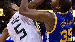 Pemain Golden State Warriors, Kevin Durant berebut bola dengan pemain Utah Jazz, Rodney Hood pada pertandingan Semifinal Wilayah Barat Playoffs NBA 2017 di Salt Lake City (5/6). (Gene Sweeney Jr / Getty Images / AFP)