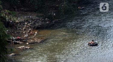 Seorang anak bermain di aliran Sungai Ciliwung, Kota Depok, Jawa Barat, Senin (27/7/2020). Setiap tanggal 27 Juli diperingati sebagai Hari Sungai Nasional, namun ironisnya kondisi sungai Ciliwung masih terlihat banyak ceceran sampah, terutama plastik. (Liputan6.com/Helmi Fithriansyah)