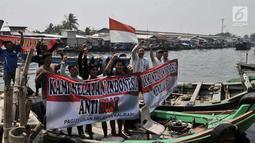 Nelayan membentangkan spanduk di atas perahu saat deklarasi antihoaks di Pelabuhan Cilincing, Jakarta Utara, Kamis (15/3). Para nelayan juga siap melaporkan jika ada berita bohong di lingkungan mereka. (Merdeka.com/Iqbal S. Nugroho)