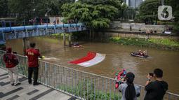Fanani) Warga menyaksikan pembentangan bendera Merah Putih di aliran kali Ciliwung di kawasan Sudirman, Jakarta, Minggu (22/8/2021). Pembentangan atau pengibaran bendera Merah Putih tersebut dilaksanakan untuk memperingati HUT ke-76 RI. (Liputan6.com/Faizal Fanani)