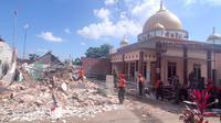 Tim relawan dan personel TNI AU (Senin, 12 April 2021) merobohkan sebuah rumah yang rusak parah di Dusun Krajan, Desa Majangtengah, Dampit, Malang, akibat gempa bumi pada 9 April 2021 (Liputan6.com/Zainul Arifin).
