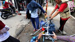 Warga korban gempa dan tsunami Palu mengambil air di mobil instalasi pengolahan air Kementerian PUPR di halaman kantor Wali Kota Palu, Sulawesi Tengah, Senin (8/10). Air bersih itu diperuntukan untuk kebutuhan rumah tangga. (Liputan6.com/Fery Pradolo)