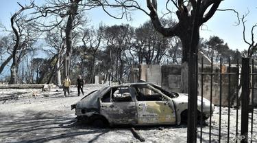 Sebuah mobil hancur dilalap api di timur Patras di Peloponnese saat Yunani memerangi kebakaran selama gelombang panas yang mengancam. (Foto: AFP/Louisa Gouliamaki)