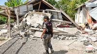 Petugas keamanan desa memeriksa rumah yang roboh akibat gempa di Lombok, NTB, Minggu (29/7). Data sementara BPBD Provinsi NTB mencatat, gempa bumi tektonik 6.4 SR itu mengakibatkan 10 orang meninggal dunia dan puluhan rumah rusak. (AFP/Aulia AHMAD)