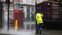 Seorang pekerja membersihkan jalan dekat Leicester Square, London, Inggris, 21 Desember 2020. Menteri Kesehatan Inggris Matt Hancock mendesak warga Inggris untuk berperilaku seolah-olah mereka sudah terjangkit virus corona COVID-19. (Xinhua/Han Yan)